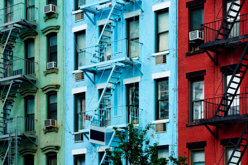 Three colorful, red, blue and green, apartment buildings facades with emergency escapes. Typical New York City, Boston or Chicago rental complexes with fire escape stairs next to the windows.