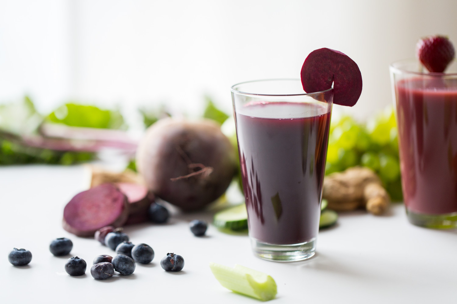 healthy eating, drinks, diet and detox concept - glass of beetroot juice with different fruits and vegetables on table